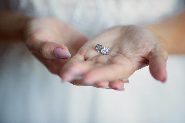 bride-holds-silver-earrings-her-arms_8353-8672
