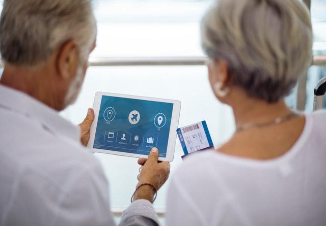Muž a žena pozerajú na letenku a tablet.jpg
