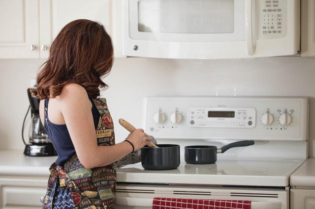 Žena stojí pri sporáku a mieša jedlo v hrnci.jpg