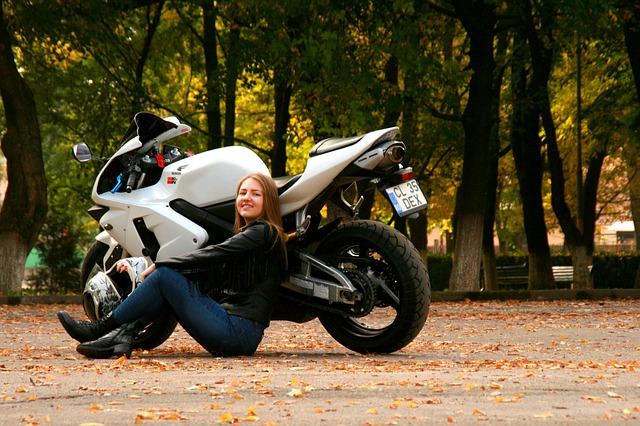 Motorkárka sedí pri športovej motorke, park.jpg