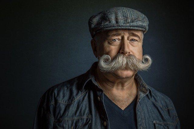Starší muž v baretke a dlhými fúzmi.jpg
