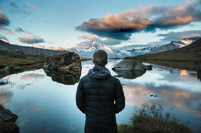 Muž v čiernej bunde stojí na okraji jazera a pozerá na veľké skaly.jpg