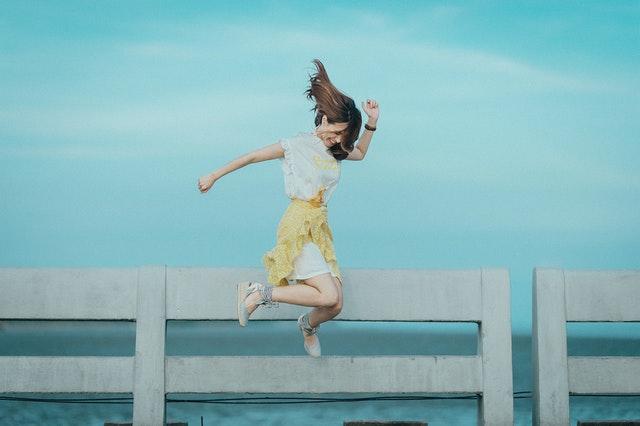 Žena vo farebnom oblečení vyskakuje do výšky.jpg
