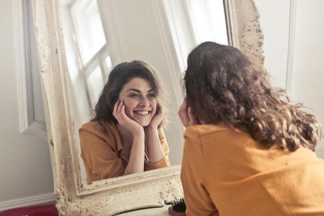 Žena s hnedými vlasmi sa pozerá do zrkadla.jpg