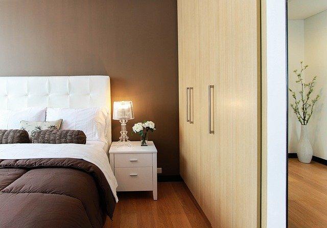 Spálňa s manželskou posteľou a nočným stolíkom, na ktorom je zapálená lampa.jpg