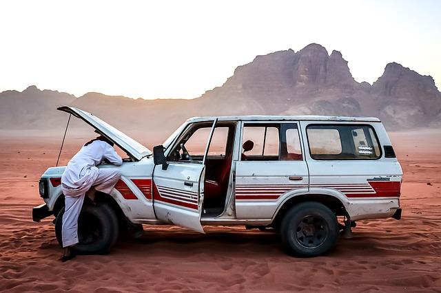 Muž opravuje auto na púšti