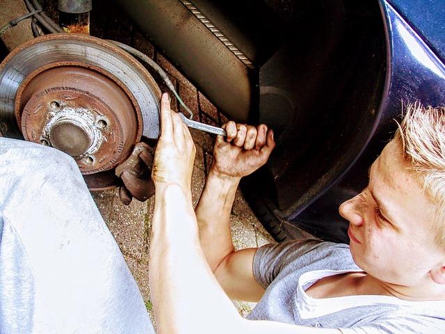 Chlapec s blond vlasmi opravuje koleso na aute
